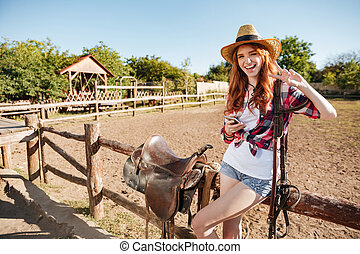 Happy young woman cowgirl with cell phone showing peace sign...