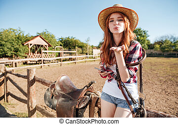 Pretty redhead cowgirl in straw hat sending air kiss while...