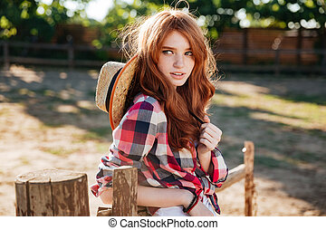 Attractive redhead young woman cowgirl standing outdoors -...