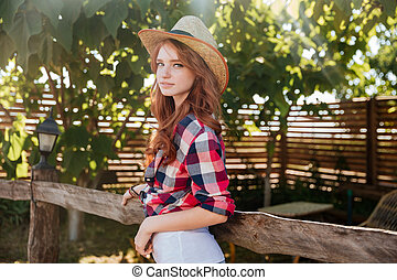 Cute smiling redhead cowgirl in hat leaning on ranch fence -...