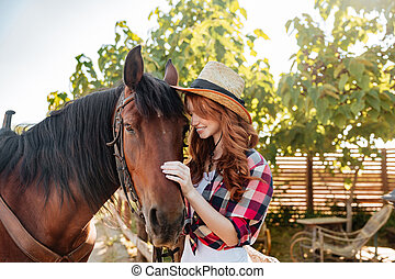 Happy young woman cowgirl standing with her horse on ranch -...