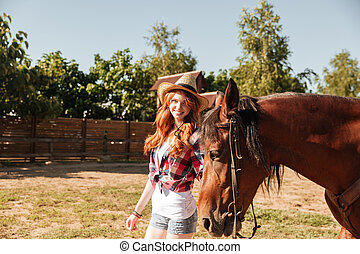 Cheerful young woman cowgirl walking wit her horse on ranch...
