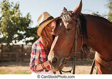 Beautiful woman cowgirl standing and kissing her horse