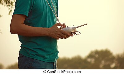 Man using drone RC remote at sunset