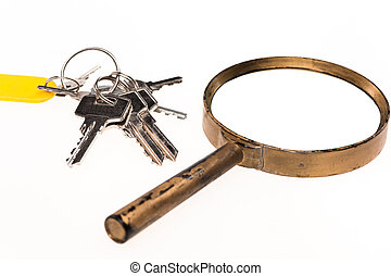 Concept image of a keys home inspection. A magnifying glass...