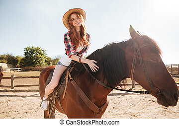 Happy woman cowgirl riding horse on ranch - Happy pretty...