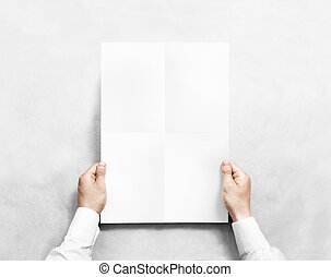 Hand holding white blank poster mockup, isolated. Arm in...