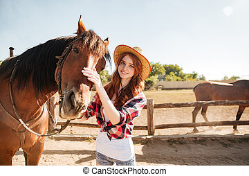 Happy woman cowgirl taking care of her horse on ranch -...