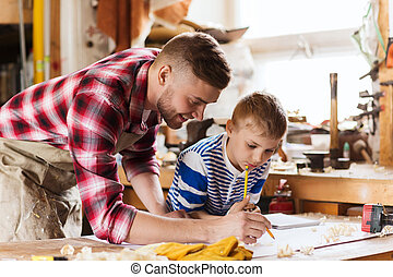 happy father and son with blueprint at workshop - family,...