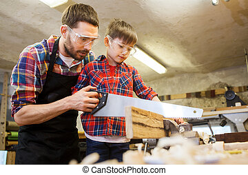 father and son with saw working at workshop - family,...