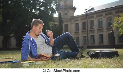 Handsome focused student studying on campus lawn - Handsome...