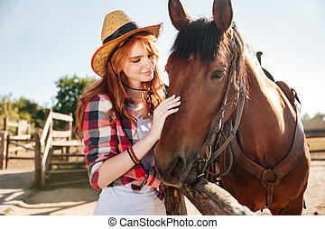Smiling tender young woman cowgirl with her horse on ranch -...