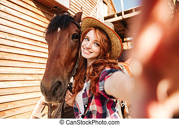 Cheerful woman cowgirl standing taking selfie with horse on...
