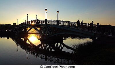 Silhouettes of arched park bridge and walking people at summer sunset