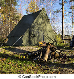Retro tent in forest and camp fire in the wild forest in...