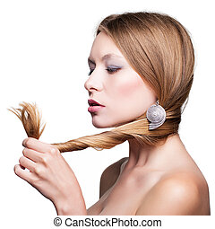 Splitting ends - Young woman looking at splitting hair ends