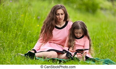 Mom with her daughter and tablet - Mom and daughter in...