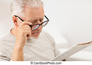 close up of old man in glasses reading newspaper - leisure,...
