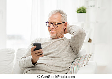 happy senior man texting on smartphone at home