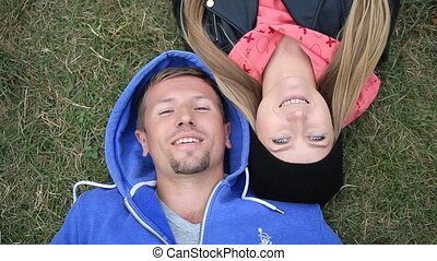 Sweethearts students lying on grass head to head -...
