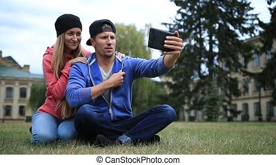 Young couple of students making selfie on tablet