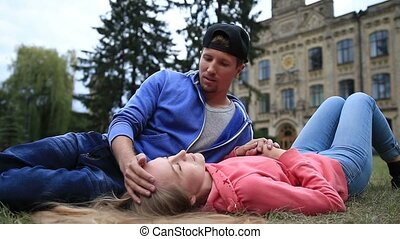 Attractive student couple resting at campus - Attractive...