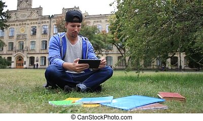 Trendy young student e-learning using tablet - Trendy young...