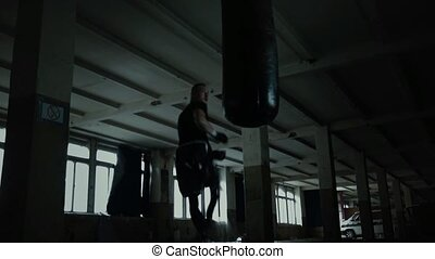 Male Athlete boxer punching bag with dramatic edgy lighting...