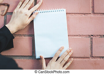 Woman holding spiral notepad - Womans hands holding blank...