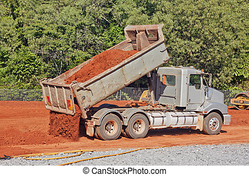 Tip truck dumping dirt on a construction site - A tip truck...