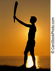 Silouetted runner with an Olympic torch at sunset