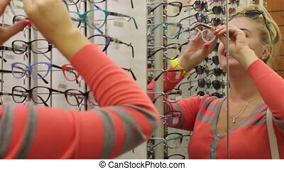 girl trying on glasses - Young woman lifts a frame for...