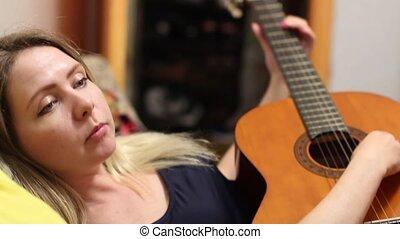 Beautiful girl adjusts guitar - Beautiful girl adjusts the...