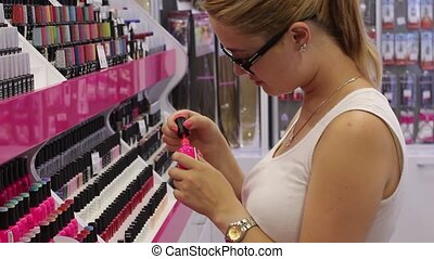 Girl chooses a color nail polish - Woman client selects the...