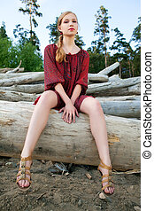 Young woman on logs in the forest - Young pretty woman on...