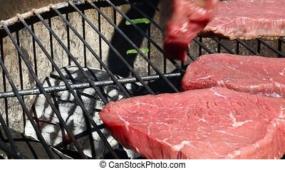 Raw beef steaks cooking on barbecue grill