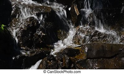 Waterfall stream of rapid water over rocky stones -...