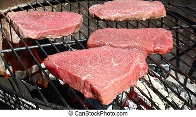 Raw beef steaks cooking on barbecue grill - Raw beef bbq...