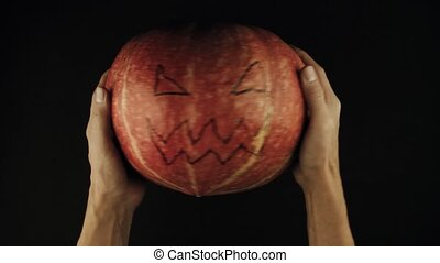 Male hands twists pumpkin with scary face jack o lantern black surface POV