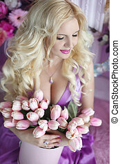 Beautiful blond woman with long wavy hair style in the purple dress holding bouquet of tulips flowers in pink Hat Box over party gifts background