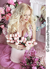Beautiful happy smiling blond woman with long wavy hair style in the purple dress holding bouquet of tulips flowers in pink Hat Box over party gifts background