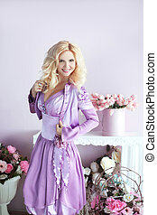 Beautiful happy smiling blond woman with long wavy hair style in the purple dress over flowers party gifts background