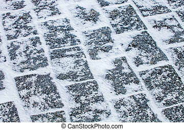 Cobblestone pavement covered with snow and ice