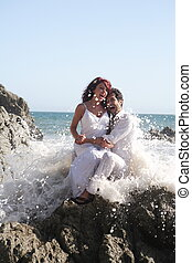 Young couple at the beach sitting on rocks while getting splashed with water