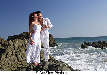 Young couple at the beach standing on rocks