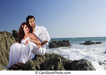 Young couple at the beach sitting on rocks and posing