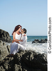 Young couple at the beach sitting on rocks and kissing