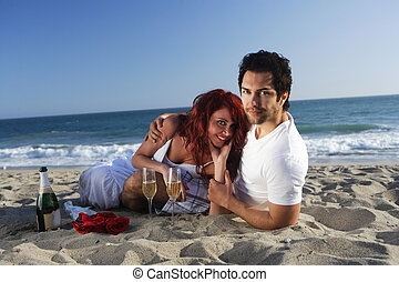 Couple at the beach with champagne and red roses