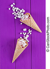 Marshmallows ice-cream and waffle cones on a purple...