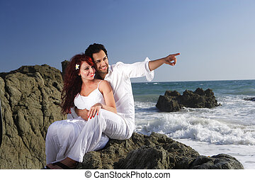 Young couple at the beach sitting on rocks and pointing